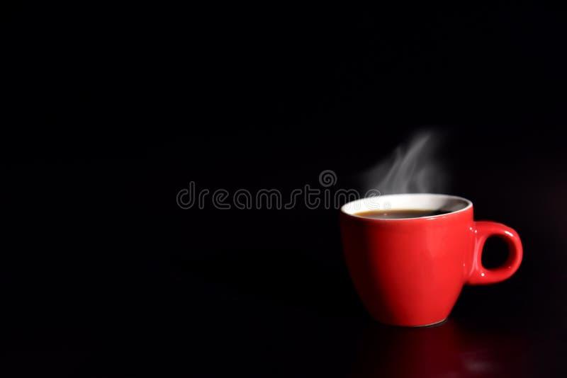 O café vermelho do copo no fundo preto para o conceito do amor, relaxa o conceito, bebendo o conceito para a propaganda, foco sel foto de stock