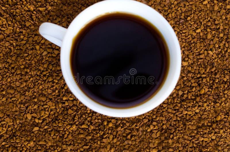 O caf? est? ao lado de um copo branco enchido com o caf? quente entre feij?es de caf? dispersados, tabela, vista superior, horizo fotografia de stock