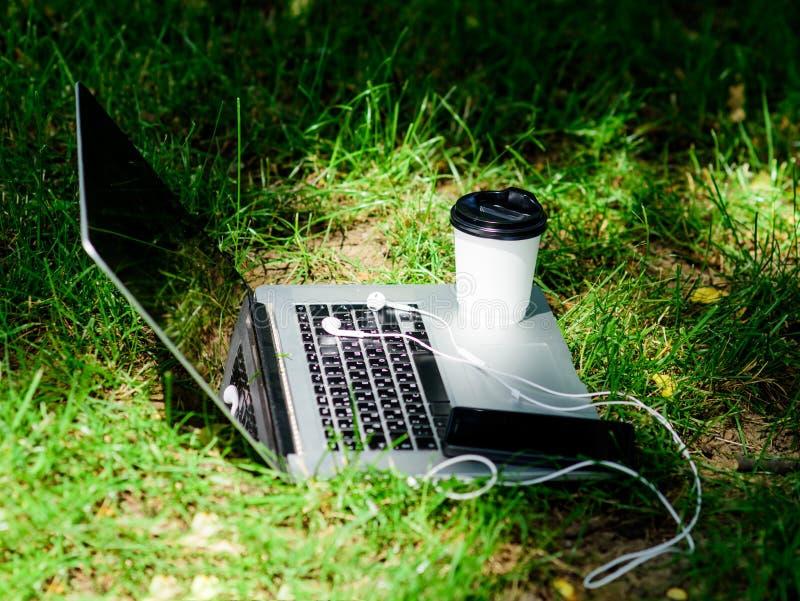 O caf? leva embora Ruptura de caf? fora Smartphone moderno do portátil com fones de ouvido e copo de café na grama verde ver?o imagem de stock royalty free