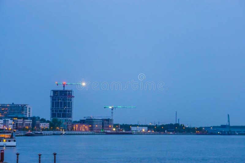 O cais da cidade de Antuérpia com água e da vista na cidade iluminada na noite, Antwerpen, Bélgica fotografia de stock royalty free