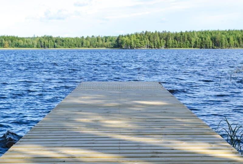O cais da pesca no lago em Finlandia rural Cais de madeira na água azul e floresta verde no dia ensolarado Ponte de madeira do mo imagem de stock