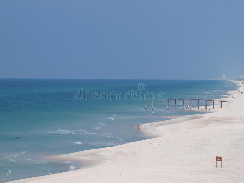 O cais das ondas de oceano da areia da praia nubla-se o céu fotos de stock