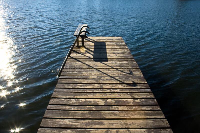 O cais de madeira bonito com banco e sol refletiu na água calma e azul imagens de stock