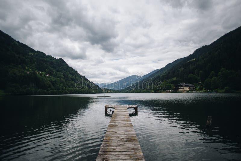 O cais de madeira entra no lago alpino pristine fotos de stock