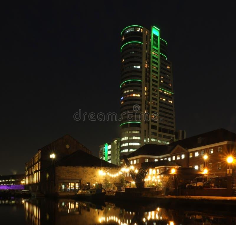 O cais do canal de Leeds na noite com constru??es brilhantemente iluminadas e no fechamento refletiu na ?gua e na incandesc?ncia  imagens de stock
