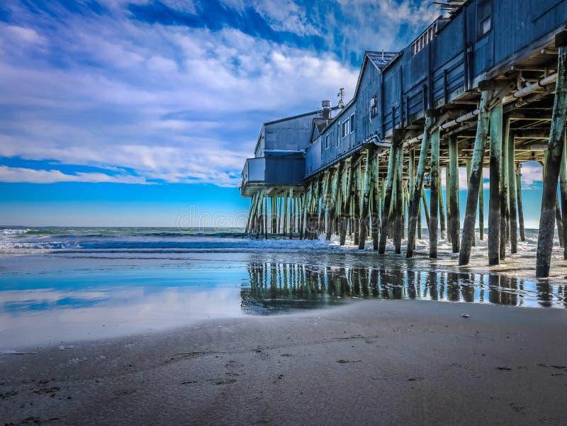 O cais no preto na praia velha do pomar fotografia de stock