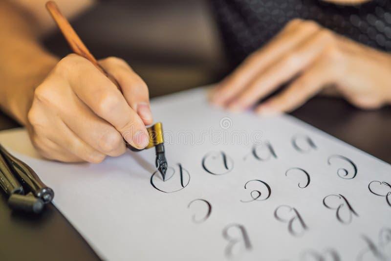 O cal?grafo Young Woman escreve a frase no Livro Branco Inscreendo letras decoradas decorativas Caligrafia, gr?fico foto de stock