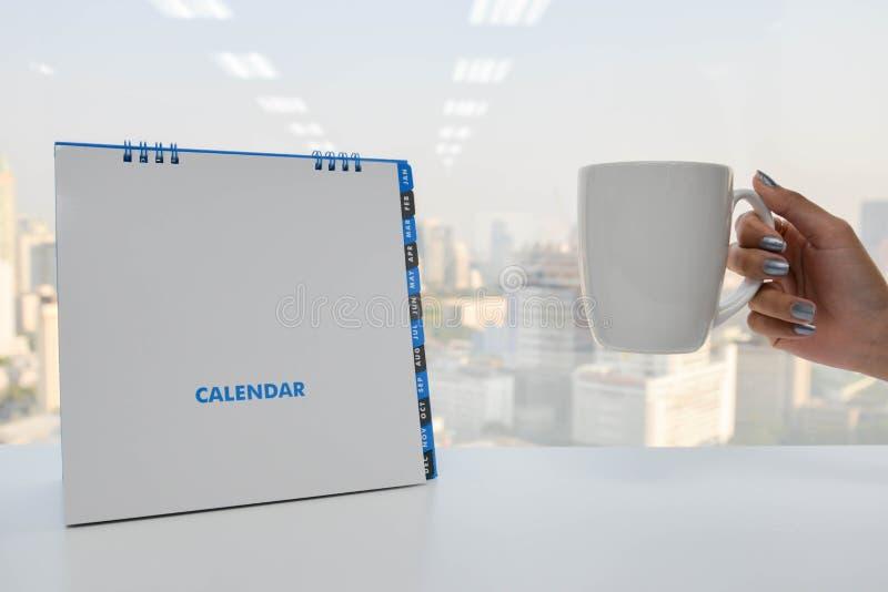O calendário e a mão brancos guardam uma xícara de café imagem de stock