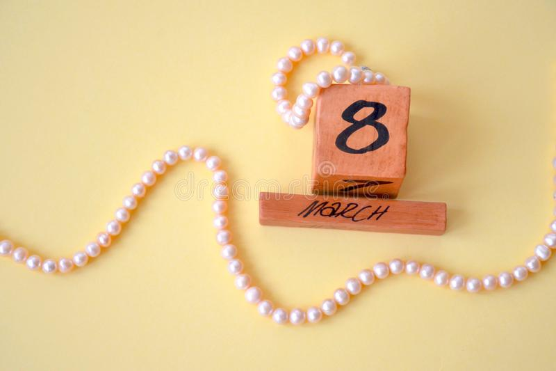 O calendário perpétuo de madeira do 8 de março e grânulos e um bracelete feito do rosa de mar natural perolizam no fundo amarelo fotografia de stock