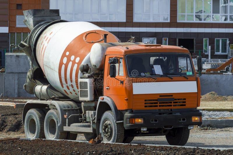 o caminhão é um caminhão com um táxi da cor alaranjada em um canteiro de obras de uma casa do arranha-céus sob a construção na ci foto de stock royalty free