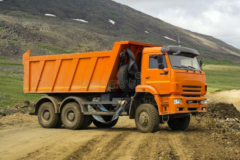 O caminhão basculante é gerencie sobre uma estrada da montanha fotos de stock royalty free