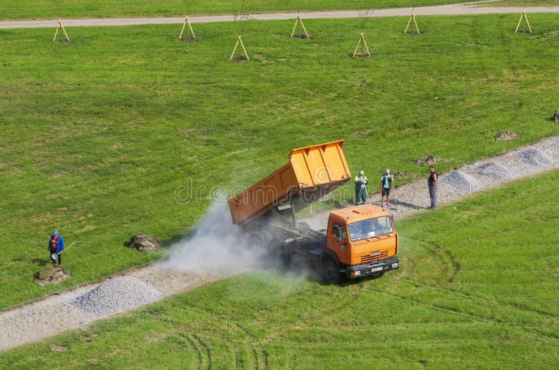 O caminhão basculante derrama o cascalho em um trajeto pedestre no quadrado de cidade imagem de stock royalty free