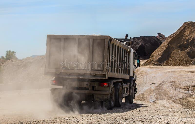 o caminhão basculante em uma estrada empoeirada entrega a pedra esmagada fotografia de stock royalty free