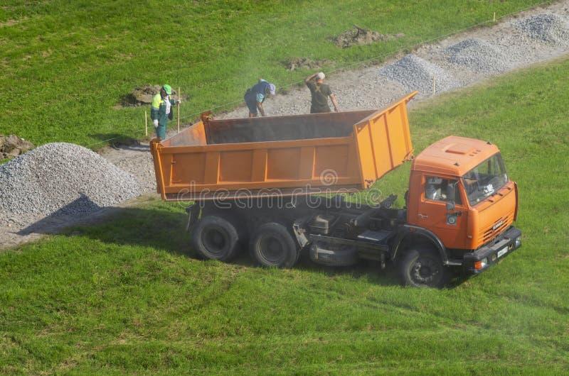 O caminhão basculante KAMAZ derramou o cascalho e aumentou nuvens da poeira fotografia de stock
