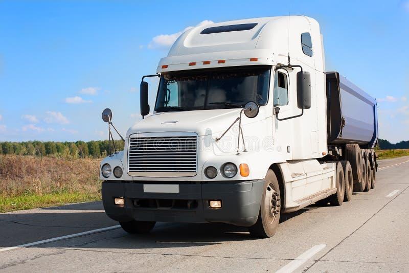 O caminhão basculante vai na estrada do país imagem de stock