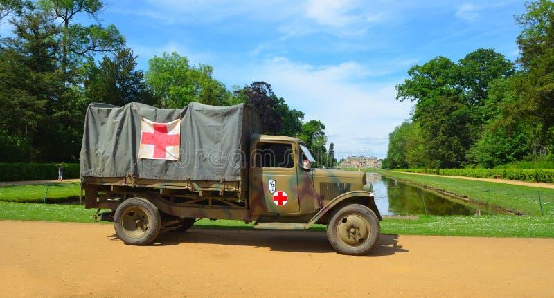 O caminhão da segunda guerra mundial do vintage com sinais da cruz vermelha estacionou com arranca a casa do parque no fundo fotografia de stock royalty free