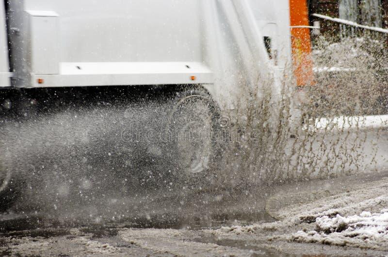 O caminhão de lixo monta na poça grande no dia nevado Respingo do granizo sobre imagem de stock royalty free