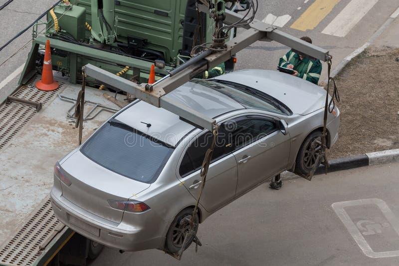 O caminhão de reboque carrega o carro para a violação das regras do estacionamento reparo fotografia de stock