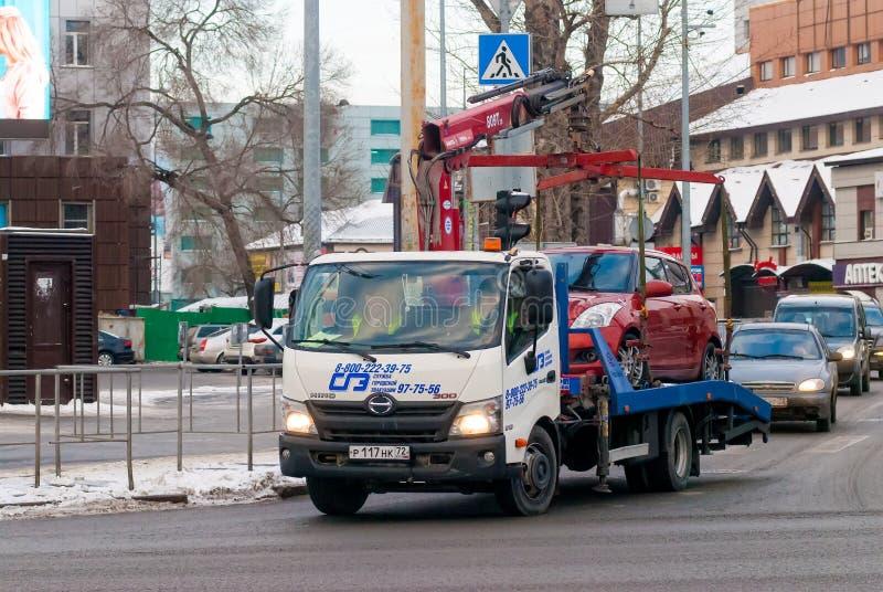 O caminhão de reboque toma o carro estacionado na violação Rússia fotografia de stock royalty free