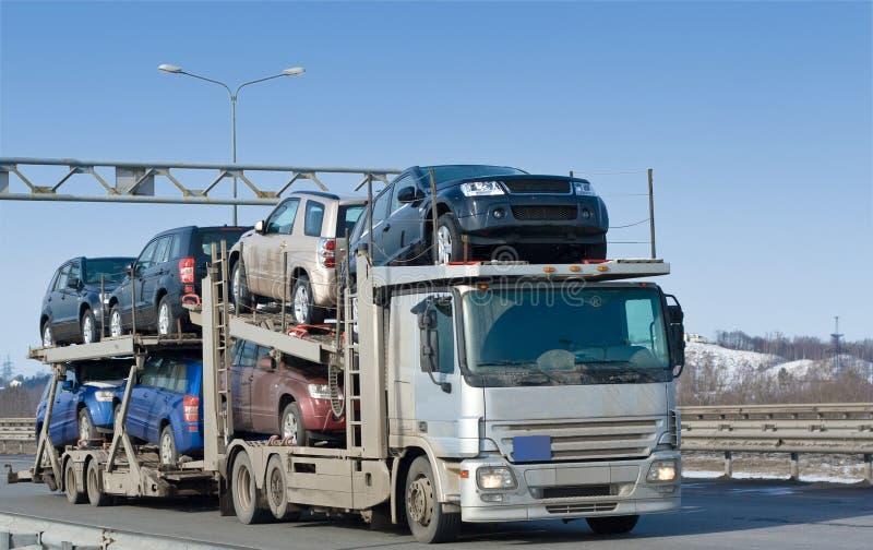 O caminhão do portador de carro entrega o auto grupo novo ao negociante fotos de stock royalty free