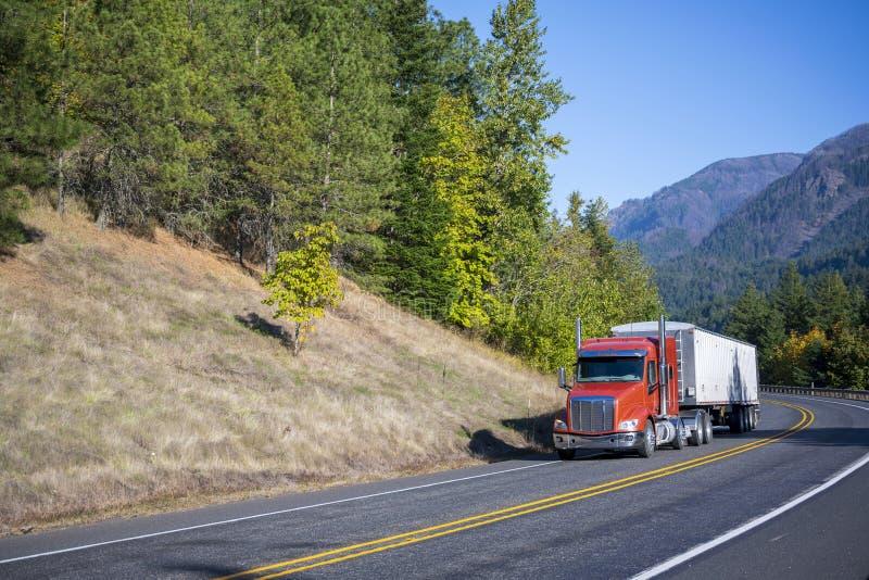 O caminhão grande da laranja do equipamento semi leva semi o reboque maioria que conduz na vitória fotografia de stock royalty free