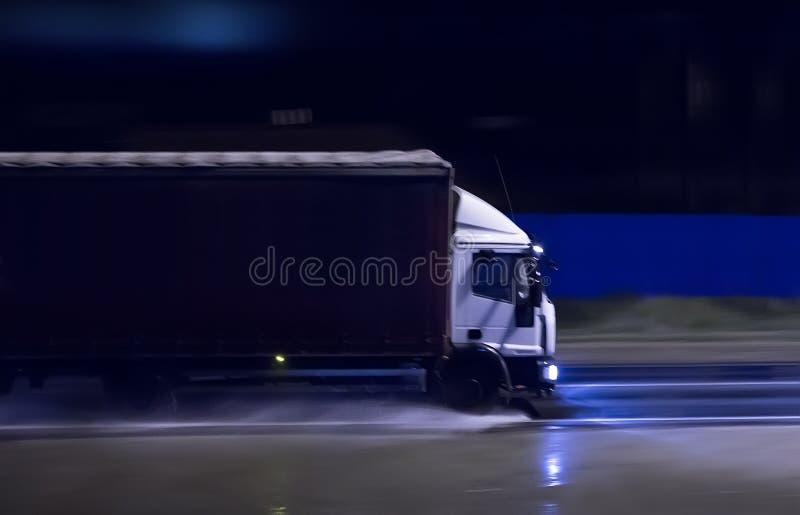 o caminhão move-se durante a noite em uma estrada molhada fotos de stock