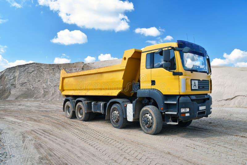 O caminhão transporta a areia em um poço de cascalho - cobrir a mineração em um aberto imagem de stock