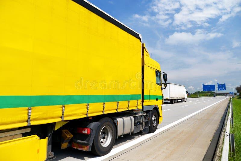 O caminhão transporta bens pela estrada - transporte e logística imagem de stock