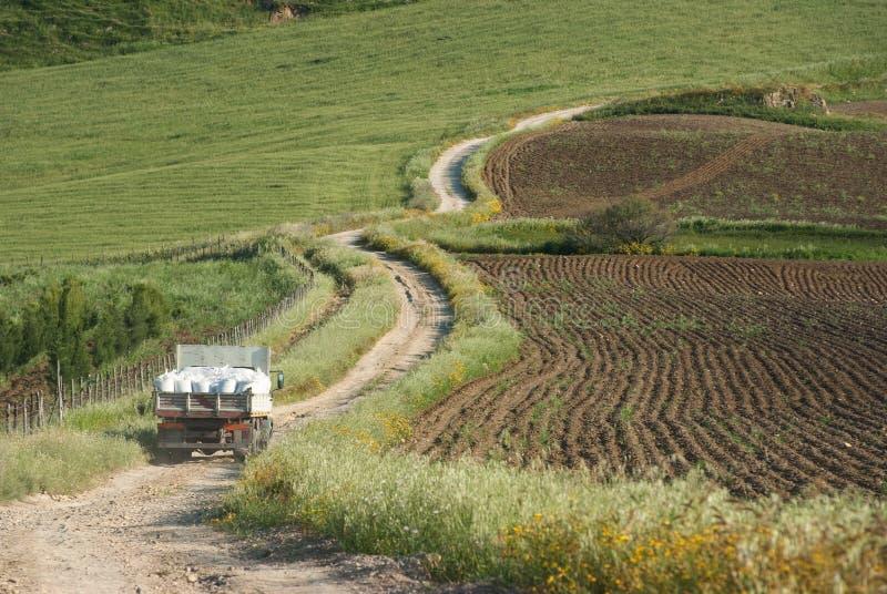 O caminhão velho cruza a estrada de terra do enrolamento na área rural fotos de stock royalty free