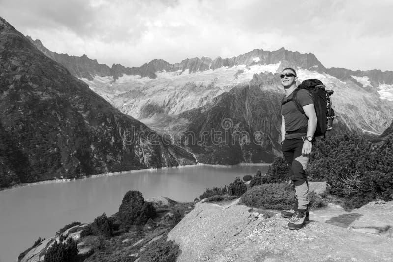 O caminhante aprecia a vista excitante de um lago da montanha fotografia de stock