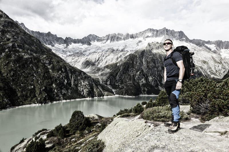 O caminhante aprecia a vista excitante de um lago da montanha nos cumes imagens de stock royalty free