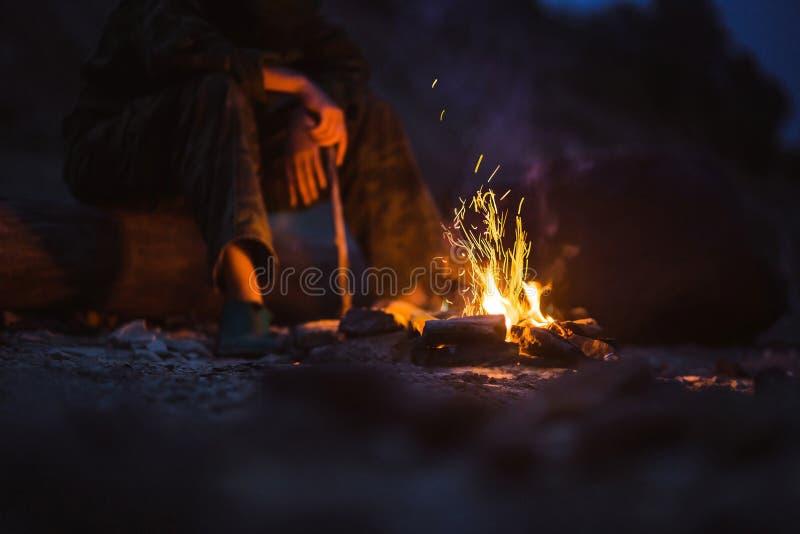O caminhante aquece seus pés ao lado de uma fogueira no crepúsculo que acampa nas madeiras imagens de stock royalty free