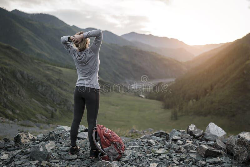 O caminhante bem sucedido da mulher adulta aprecia a vista na parte superior o da borda do penhasco imagem de stock royalty free