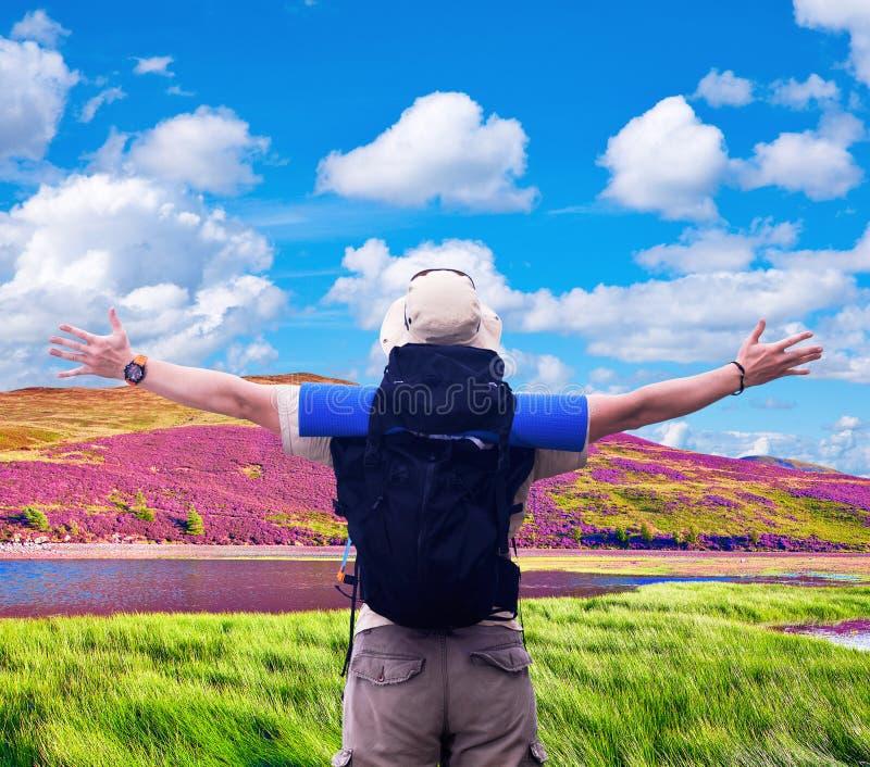 O caminhante com mochila preta espalha as mãos que expressam a felicidade fotografia de stock