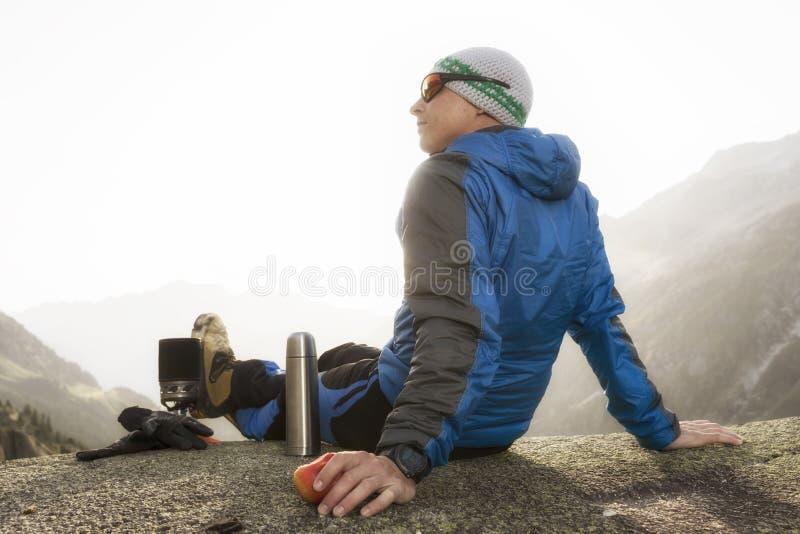 O caminhante come uma maçã durante uma ruptura e prepara um chá quente fotos de stock royalty free