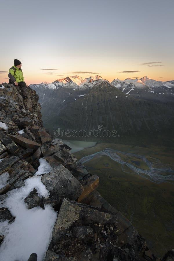 O caminhante corajoso que senta-se na borda de um penhasco rapadalen dentro o vale com backgorund da montanha do por do sol imagens de stock