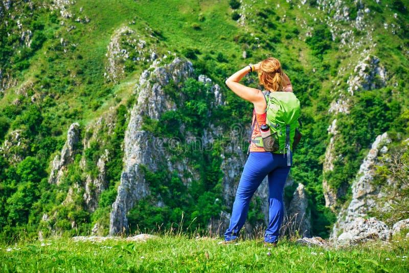 O caminhante da jovem mulher com uma trouxa verde está em um cume e em olhares da grama para as paredes maciças da rocha no desfi fotografia de stock royalty free