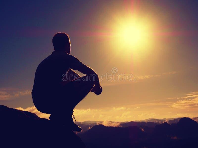 O caminhante da liberdade senta acima o vale enevoado e aprecia a manhã na natureza bonita imagem de stock