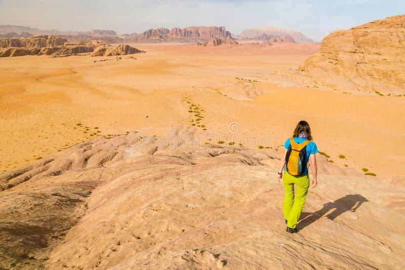 O caminhante da moça acima das dunas de areia vermelhas abandona, Wadi Rum, Jordânia, Médio Oriente foto de stock