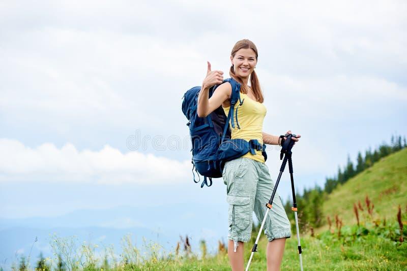 O caminhante da mulher que caminha no monte gramíneo, trouxa vestindo, usando trekking cola nas montanhas foto de stock