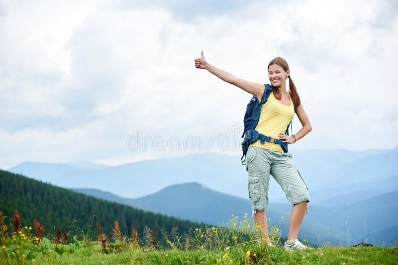 O caminhante da mulher que caminha no monte gramíneo, trouxa vestindo, usando trekking cola nas montanhas fotos de stock royalty free