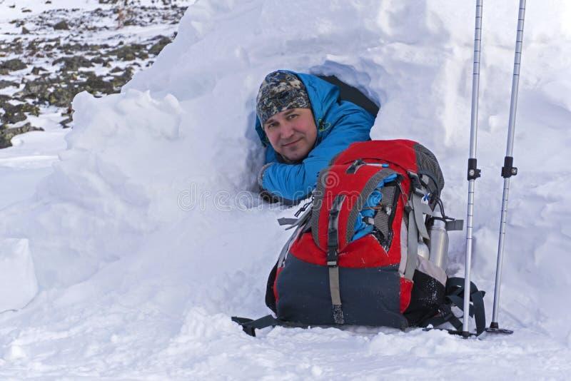 O caminhante de sorriso olha fora de um iglu nevado da cabana no inverno fotografia de stock royalty free