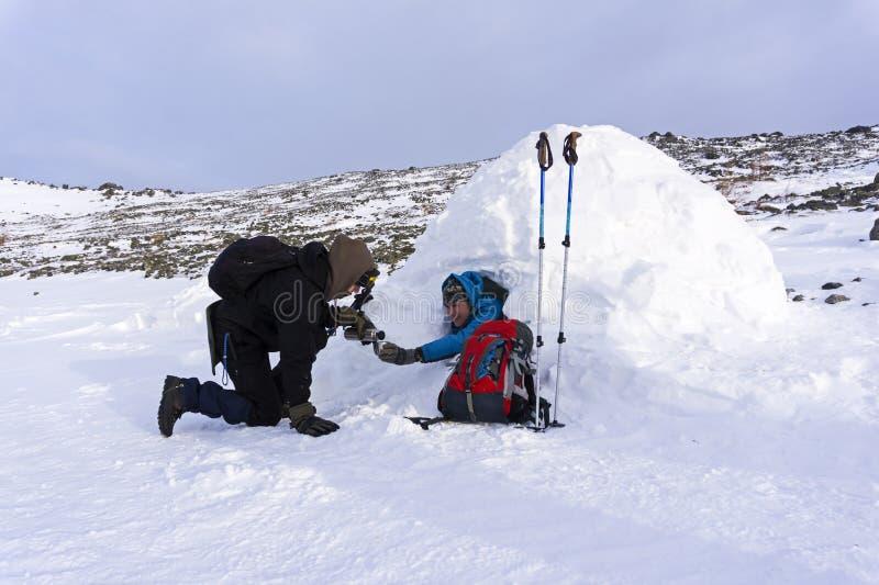 O caminhante derrama o chá de sua garrafa térmica a seu amigo que senta-se em um iglu nevado da casa fotos de stock
