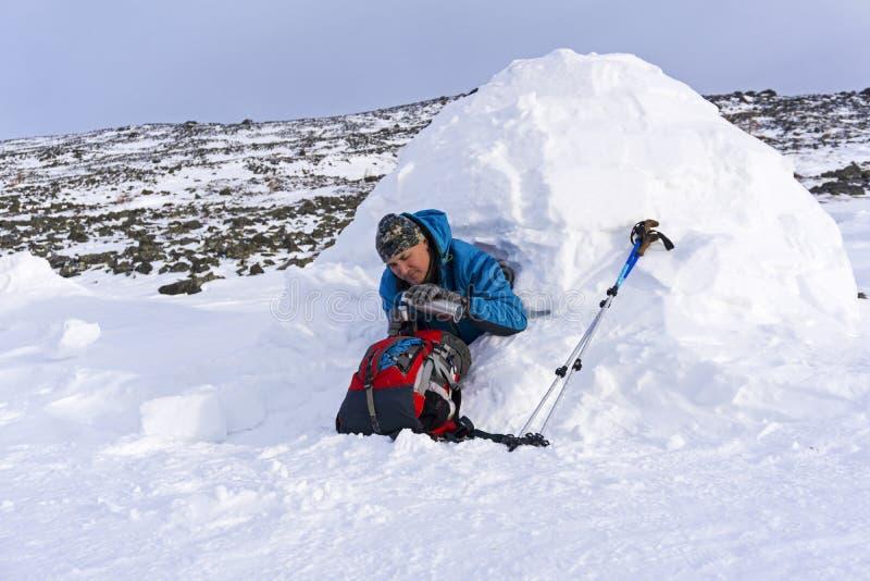 O caminhante derrama-se um chá de uma garrafa térmica, sentando-se em um iglu nevado da casa imagens de stock