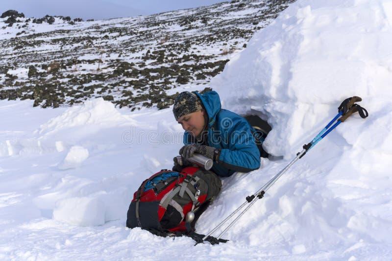 O caminhante derrama-se uma bebida quente de uma garrafa térmica, sentando-se em um iglu nevado da casa imagem de stock royalty free