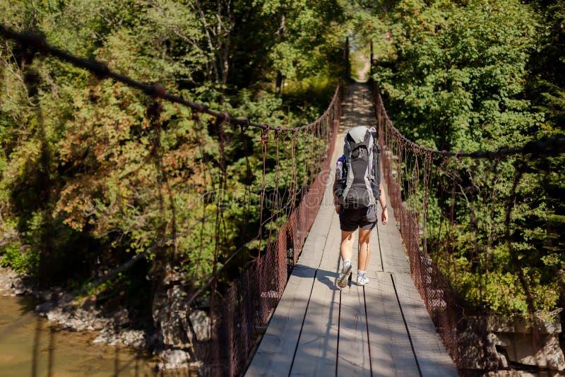 O caminhante está cruzando a ponte de suspensão fotografia de stock