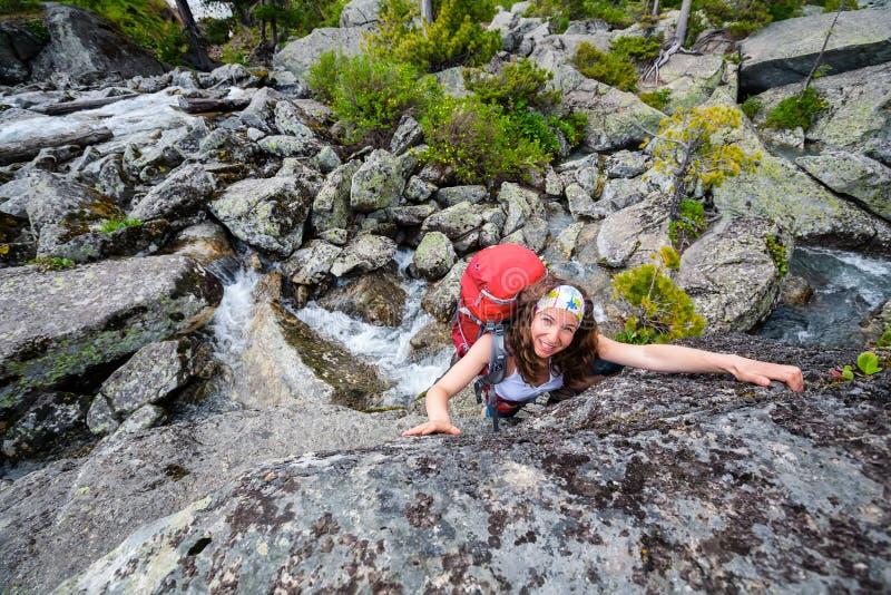 O caminhante está escalando a inclinação rochosa da montanha em montanhas de Altai, Ru foto de stock