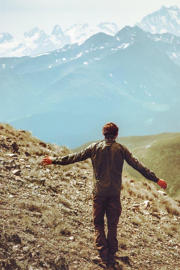 O caminhante feliz do homem apenas em montanhas levantou as mãos imagem de stock royalty free
