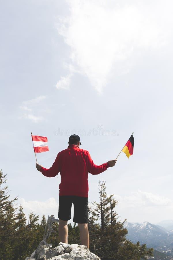 O caminhante masculino com camiseta vermelha está guardando duas bandeiras fotografia de stock