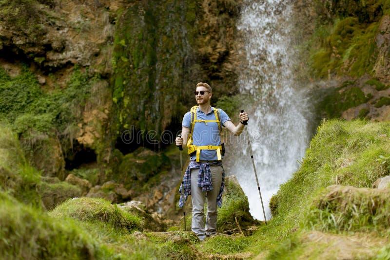 O caminhante novo parou ao lado de uma cachoeira da montanha para descansar imagens de stock royalty free